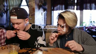 Hipsters eating delicious roasted chicken wings
