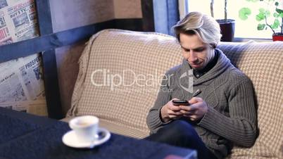 Young hipster guy texting on mobile phone