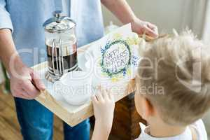 Father and son holding tray with card