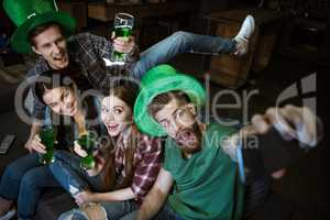 high angle view of friends with beer making selfie on St.Patrick's day