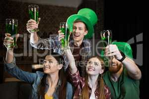 cheerful friends holding glasses with beer on St. Patrick's day celebration