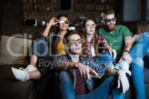 young friends in 3D glasses watching movie at home