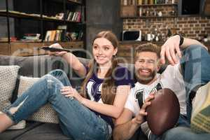 portrait of happy stylish couple watching sports game at home