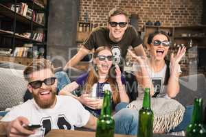 excited young friends in 3D glasses watching movie on sofa at home