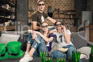 young friends in 3D glasses watching movie on sofa at st patricks day