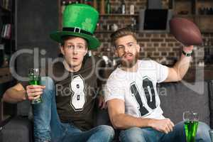 Emotional young men with watching football match at st patricks day