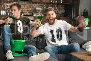 Excited young men with beer glasses watching football match at st patricks day