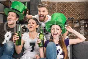Happy young friends in green hats drinking beer and celebrating st patricks day