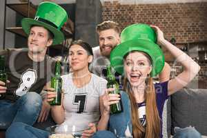 Happy young friends in hats drinking green beer and celebrating st patricks day