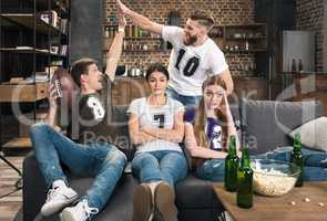 Bored young women sitting near excited men supporting favorite football team at home