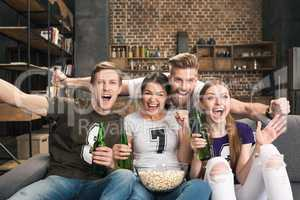 Excited young friends drinking beer and eating popcorn cheering at camera