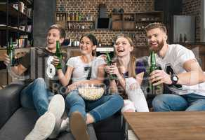 Cheerful young friends holding beer bottles and looking away at home