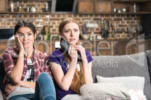 Young scared women sitting on sofa and watching tv