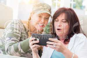 Two Female Friends Laugh While Using A Smart Phone