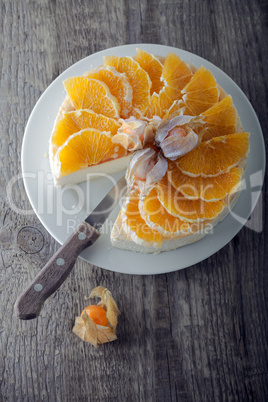 Cheesecake decorated with oranges and physalis.