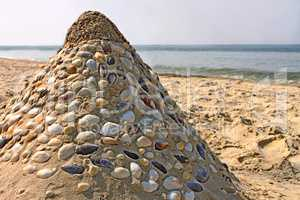 Sandy pyramid with shells on a sea beach