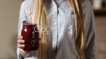 Female hand holding fresh beet smoothie in jar