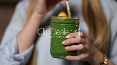 Woman drinking green detox vegetable smoothie