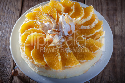 Cheesecake decorated with oranges and physalis