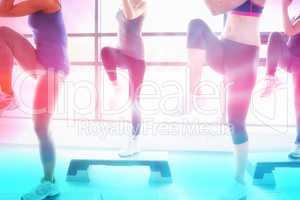 Composite image of women raising their legs while doing aerobics