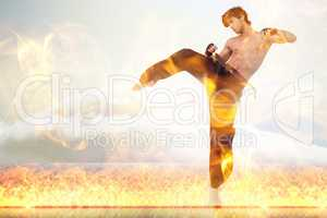 Composite image of martial arts fighter over fire flames