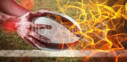 Composite image of hand rugby ball against abstract orange glowing black background