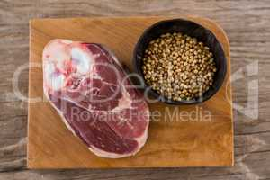 Sirloin chop and coriander seeds on wooden tray