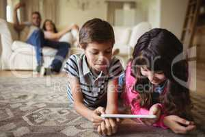 Sibling lying on rug and using digital tablet in living room