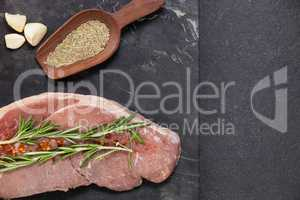 Sirloin chop, garlic and spices on black slate plate