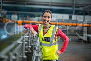 Smiling female factory worker standing next to production line
