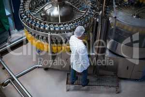Factory engineer monitoring filled juice bottle on production line