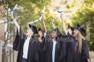 Smiling graduate school kids standing with degree scroll in campus