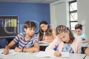 Attentive school kids doing homework in classroom
