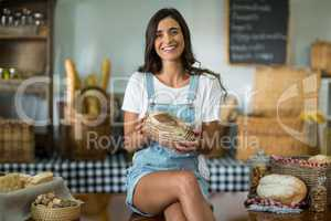 Portrait of smiling woman sitting at counter holding a round loaf of bread