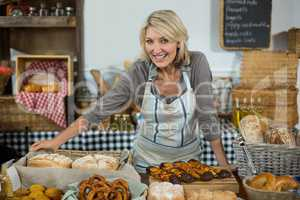 Portrait of female staff standing at counter in bake shop