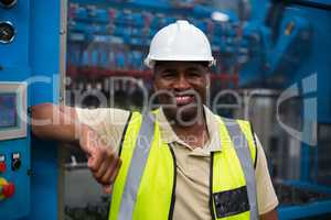 Portrait of smiling factory worker leaning on machine control cabinet
