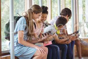 Happy students sitting on window sill and using mobile phone in corridor