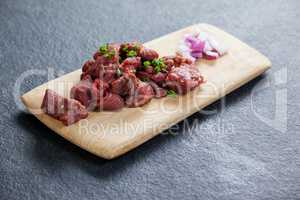 Diced beef and onions on wooden board