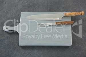 Knife and fork on wooden board