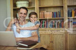 Portrait of father and son using laptop in study room