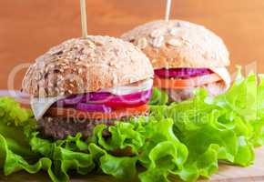 Cheeseburger with salad, onion, tomato and fresh bread