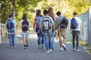 Rear vie of school kids walking on road in campus