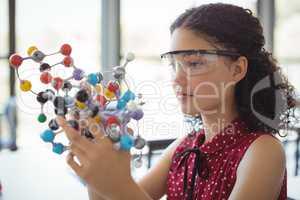 Attentive schoolgirl experimenting molecule model in laboratory