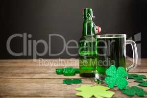 Mug of green beer, beer bottle and shamrocks for St Patricks Day