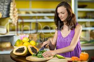 Shop assistant chopping leaf vegetable at counter