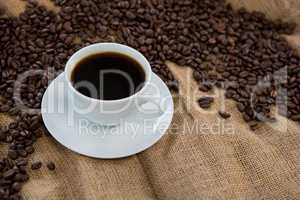 Coffee cup with coffee beans on sack