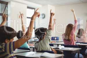 School kids raising hand in classroom