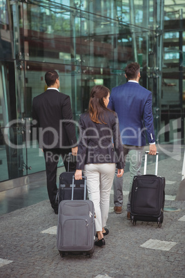 Business executives walking with suitcase outside platform