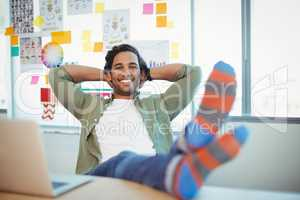 Male graphic designer relaxing with feet up at desk