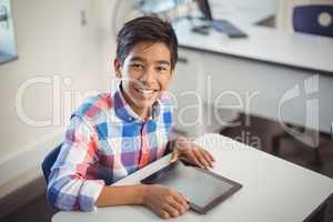 Schoolboy with digital tablet at desk